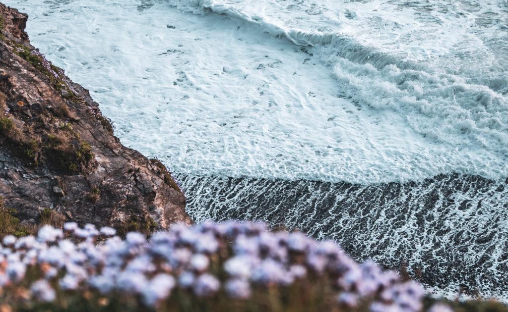 Meer in Cornwall - Welle schwappt über Felsen.